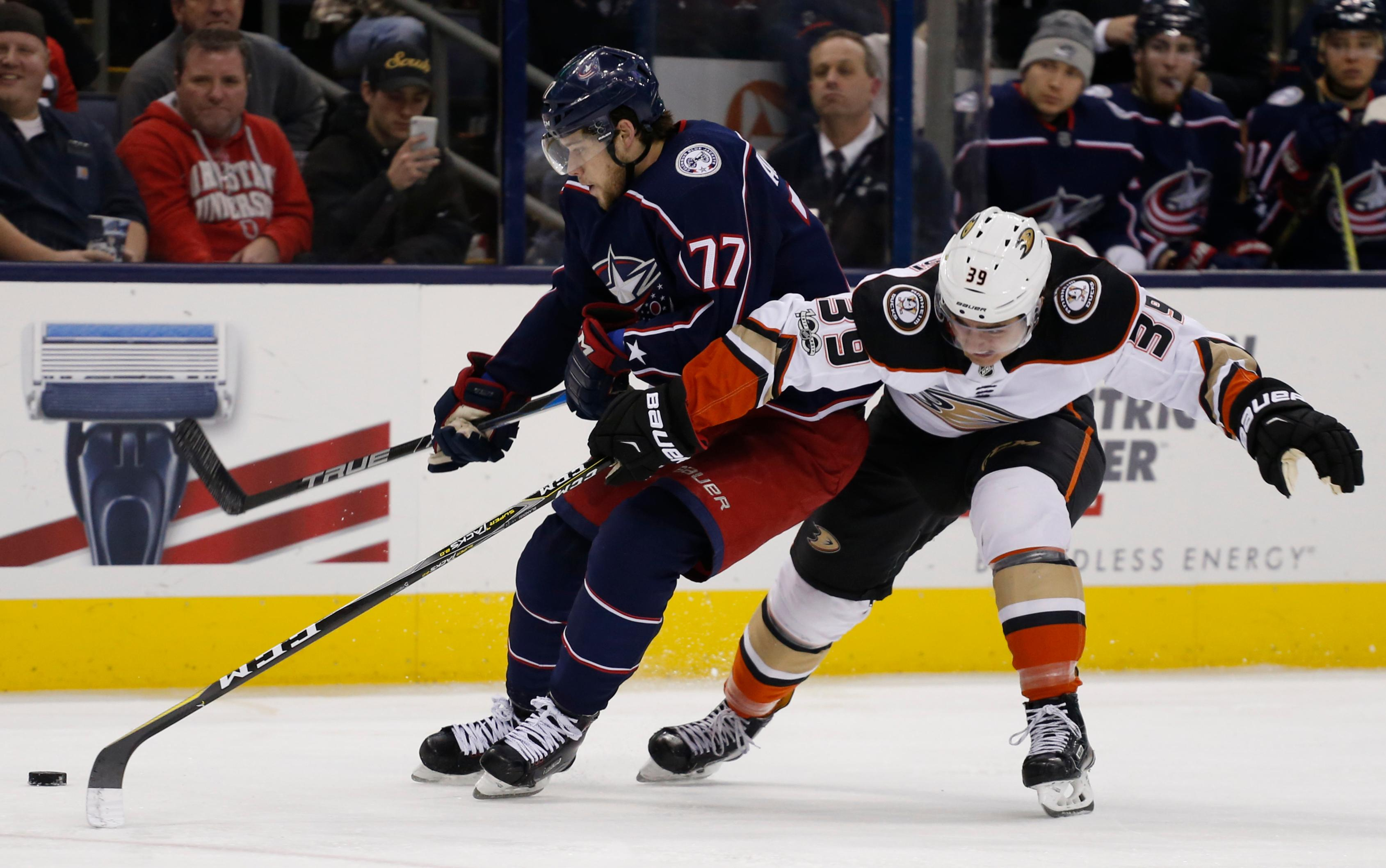 Columbus Blue Jackets' Josh Anderson, left, carries the puck upice as Anaheim Ducks' Joseph Blandisi defends during the second period of an NHL hockey game Friday, Dec. 1, 2017, in Columbus, Ohio. (AP Photo/Jay LaPrete)
