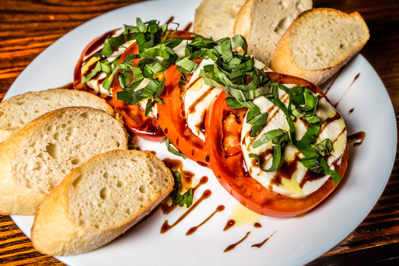 Mozzarella Caprese Salad: tomatoes, fresh mozzarella, fresh basil, extra virgin olive oil, drizzled with balsamic glaze and served with baguette slices / Image: Catherine Viox // Published: 11.25.19