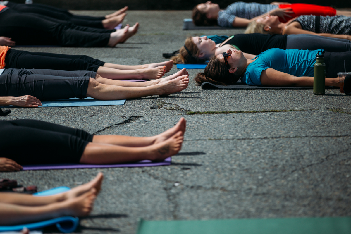 There's something very therapeutic about the idea of doing yoga in the middle a street in Fremont on a Sunday morning. That's exactly what dozens of people did, led by yoga teacher, Laura Yon, as part of the Fremont Fair. June 22nd 2014. (Joshua Lewis / Seattle Refined)