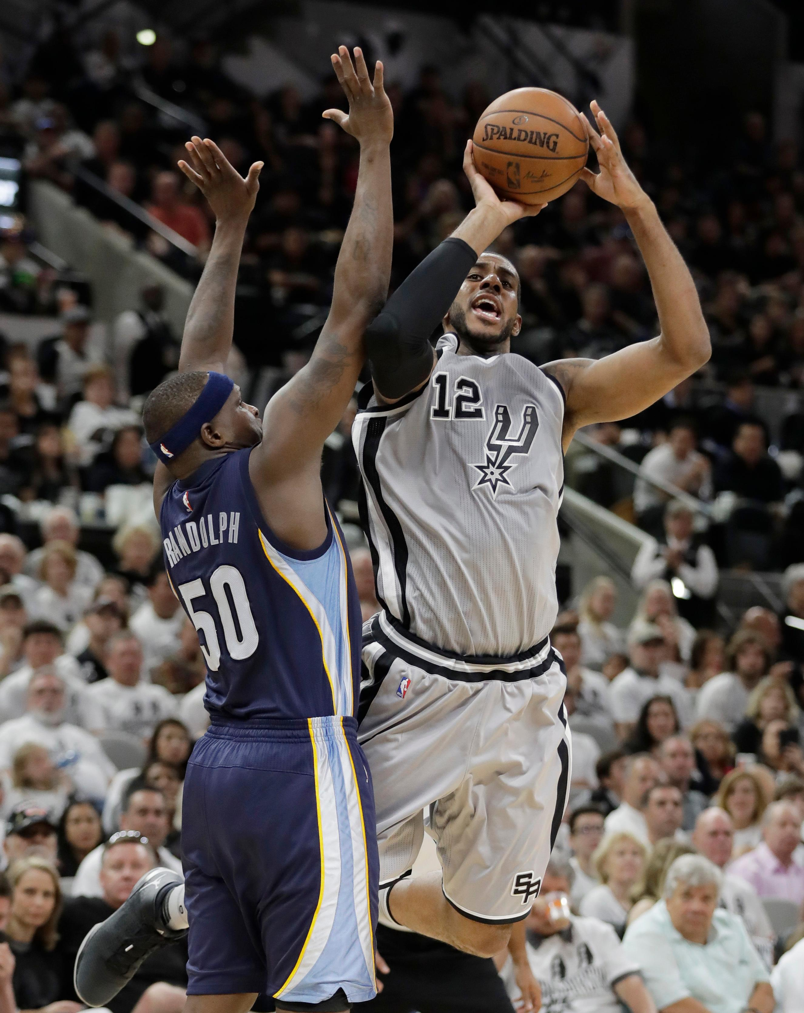San Antonio Spurs forward LaMarcus Aldridge (12) shoots over Memphis Grizzlies forward Zach Randolph (50) during the second half in Game 1 of a first-round NBA basketball playoff series, Saturday, April 15, 2017, in San Antonio. (AP Photo/Eric Gay)