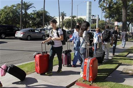 Passengers walk with their luggage on a city street outside Los Angeles International Airport on Friday.