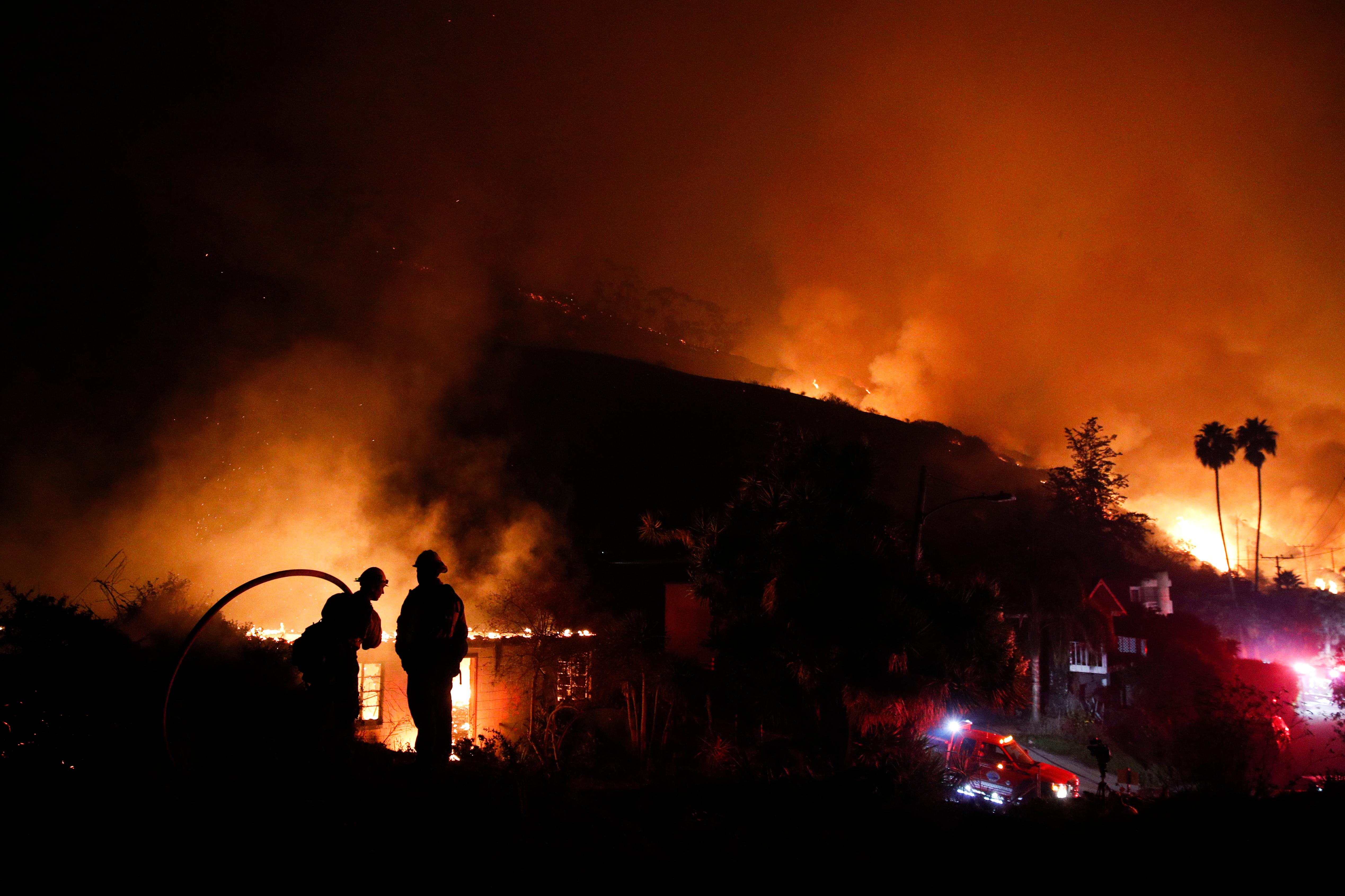 Two firefighters watch as a home burns in a wildfire in La Conchita, Calif., Thursday, Dec. 7, 2017. The wind-swept blazes have forced tens of thousands of evacuations and destroyed dozens of homes. (AP Photo/Jae C. Hong)