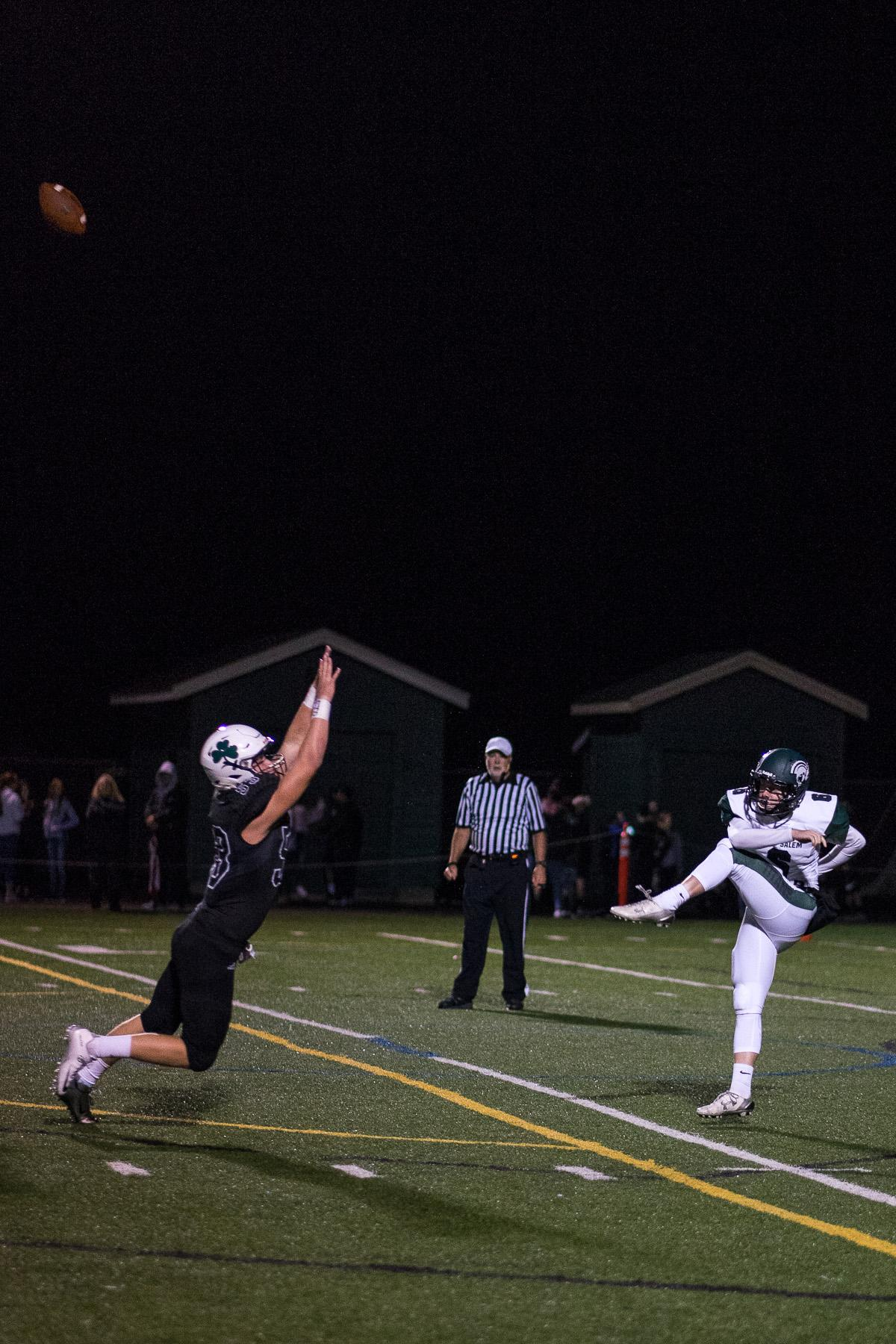 West Salem's Andrew Bartholomew (#6) punts the ball past Sheldon's defense. On a rainy Monday evening, Sheldon defeated West Salem at home 41 – 7. The game had been postponed until Monday, September 18, due to unhealthy levels of smoke in the air caused by nearby forest fires. Photo by Kit MacAvoy, Oregon News Lab
