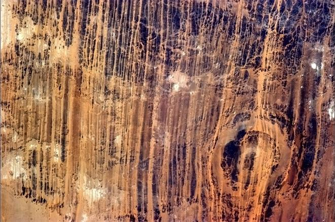 An ancient crater in the hard rock, blasted by sand, NE Africa. Maybe a meteor crater?  (Photo & Caption: Chris Hadfield/NASA)