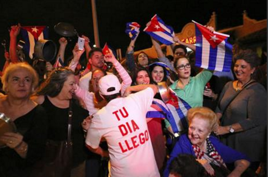 The Cuban community celebrates the announcement that Fidel Castro died as they gather in front La Carreta Restaurant early Saturday, Nov. 26, 2016, in Miami. Within half an hour of the Cuban government's official announcement that former President Fidel Castro had died, Friday, Nov. 25, 2016, at age 90, Miami's Little Havana teemed with life - and cheers. (David Santiago/El Nuevo Herald via AP)