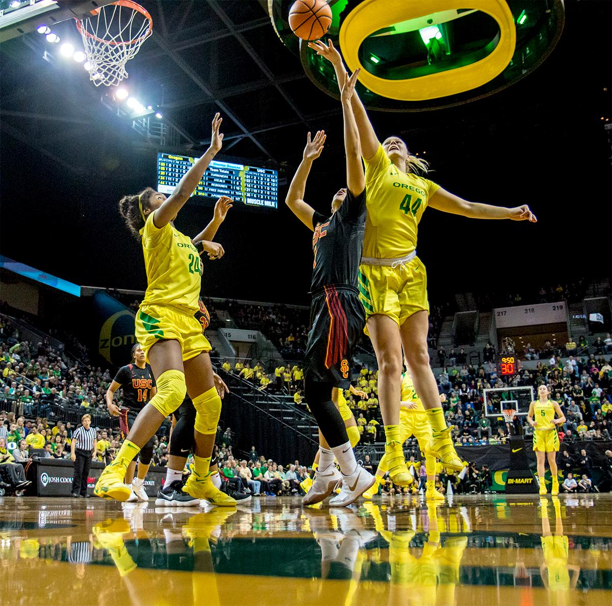 The Duck's Mallory McGwire (#44) jumps up to catch the rebound. The Oregon Ducks defeated the USC Trojans 80-74 on Friday at Matthew Knight Arena in a  game that went into double overtime. Lexi Bando sealed the Ducks victory by scoring a three-pointer in the closing of the game. Ruthy Hebard set a new NCAA record of 30 consecutive field goals, the old record being 28. Ruthy Hebard got a double-double with 27 points and 10 rebounds, Mallory McGwire also had 10 rebounds. The ducks had four players in double digits. The Ducks are now 24-4, 13-2 in the Pac-12, and are tied for first with Stanford. Photo by August Frank, Oregon News Lab