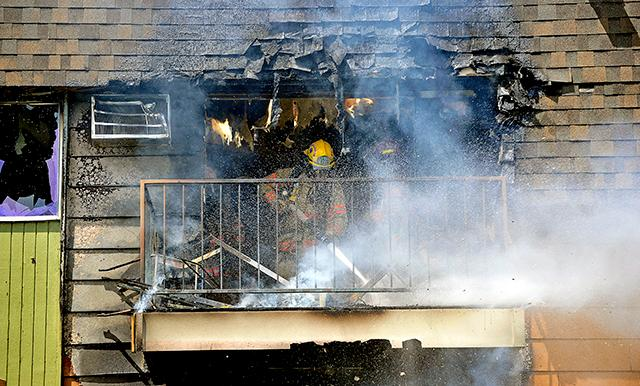 Jamie Lusch / Mail Tribune Firefighters work to put a fire at Valley Pines on Royal Avenue in Medford.