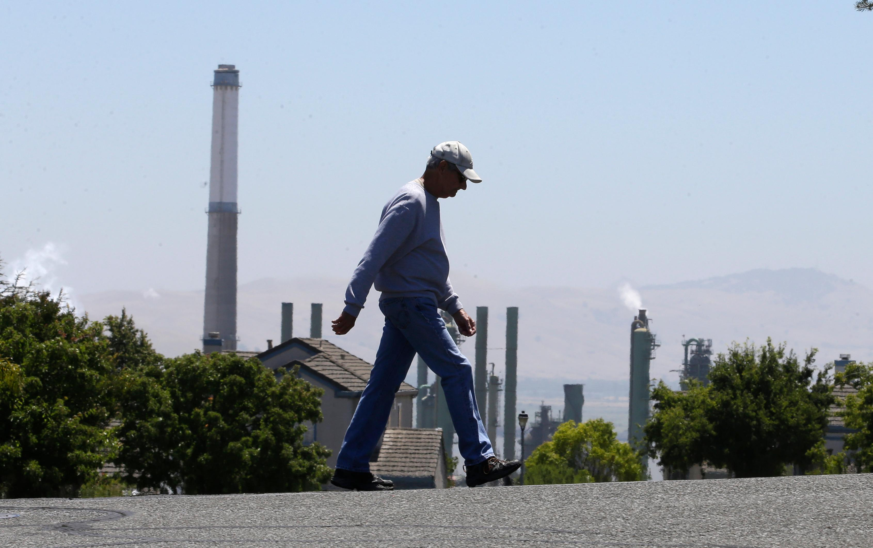 "File- In this July 12, 2017 file photo the stacks from the Valero Benicia Refinery are seen as a pedestrian walks in a nearby neighborhood, in Benicia, Calif. Gov. Jerry Brown and state lawmakers got national attention last month for extending the state's ""cap and trade"" climate change law that keeps alive a program that raises hundreds of millions of dollars a year by auctioning off permits to release climate-changing gases.  California lawmakers return Monday, Aug. 21 , from a monthlong break with a busy agenda that includes tackling the state's housing crisis and deciding whether to make California a statewide sanctuary for people living illegally in the U.S. (AP Photo/Rich Pedroncelli, file)"