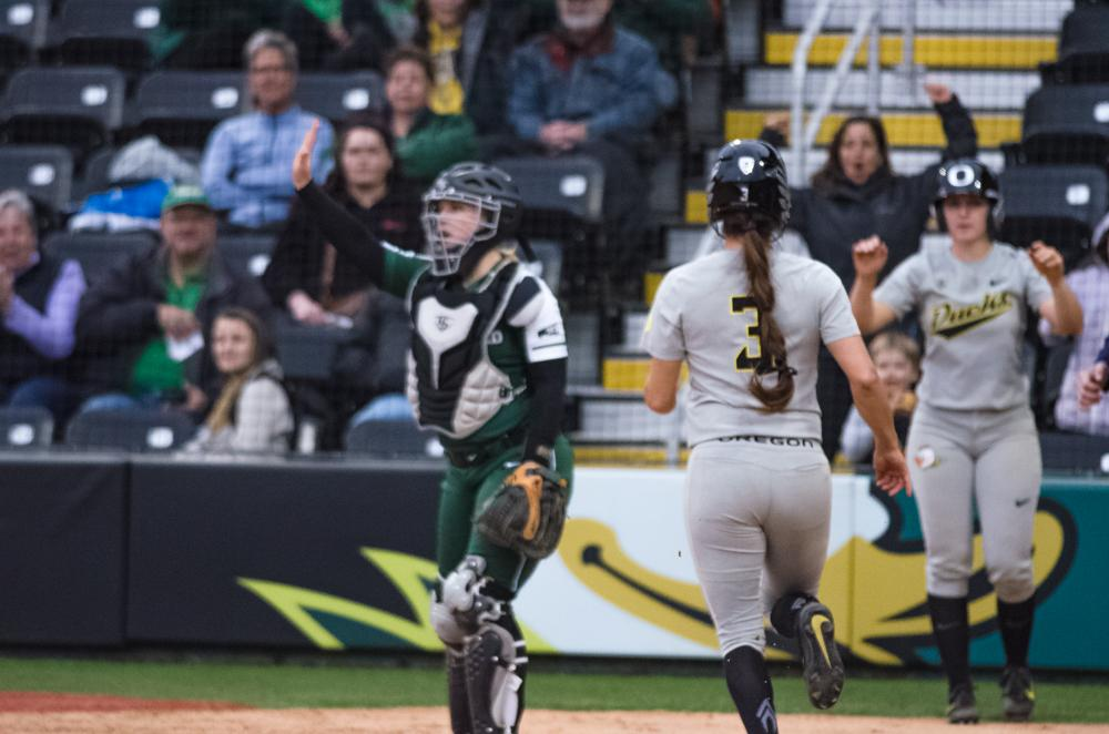 Oregon Ducks Nikki Udria (#3) rounds home plate for the score. The Ducks are now 35-0 this season matching a NCAA record for most consecutive wins to start a season, winning the first game 3-1 then following up with a 8-0 win in the second and will next play UCLA on April 7th in Los Angeles, California. Photo by Jonathan Booker, Oregon News Lab