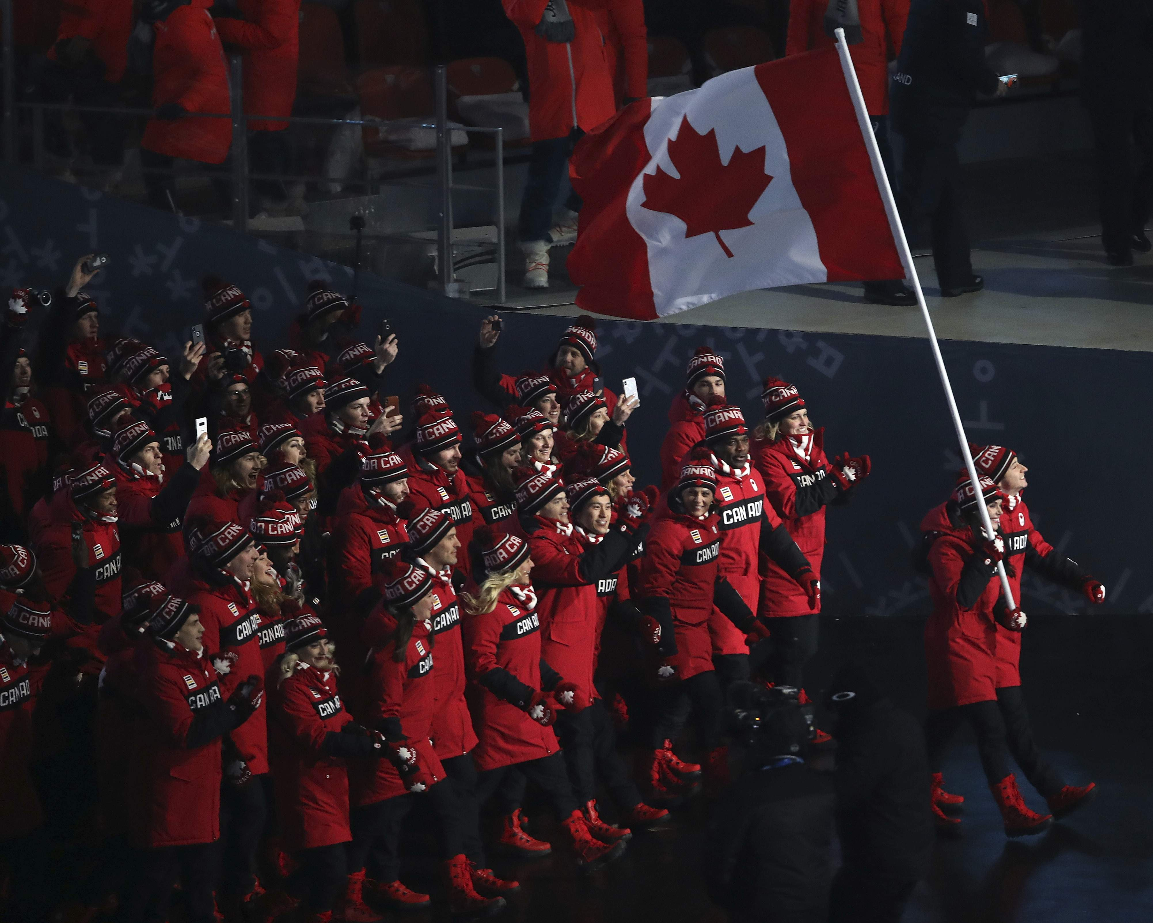 Tessa Virtue carries the flag of Canada during the opening ceremony of the 2018 Winter Olympics in Pyeongchang, South Korea, Friday, Feb. 9, 2018. (Sean Haffey/Pool Photo via AP)