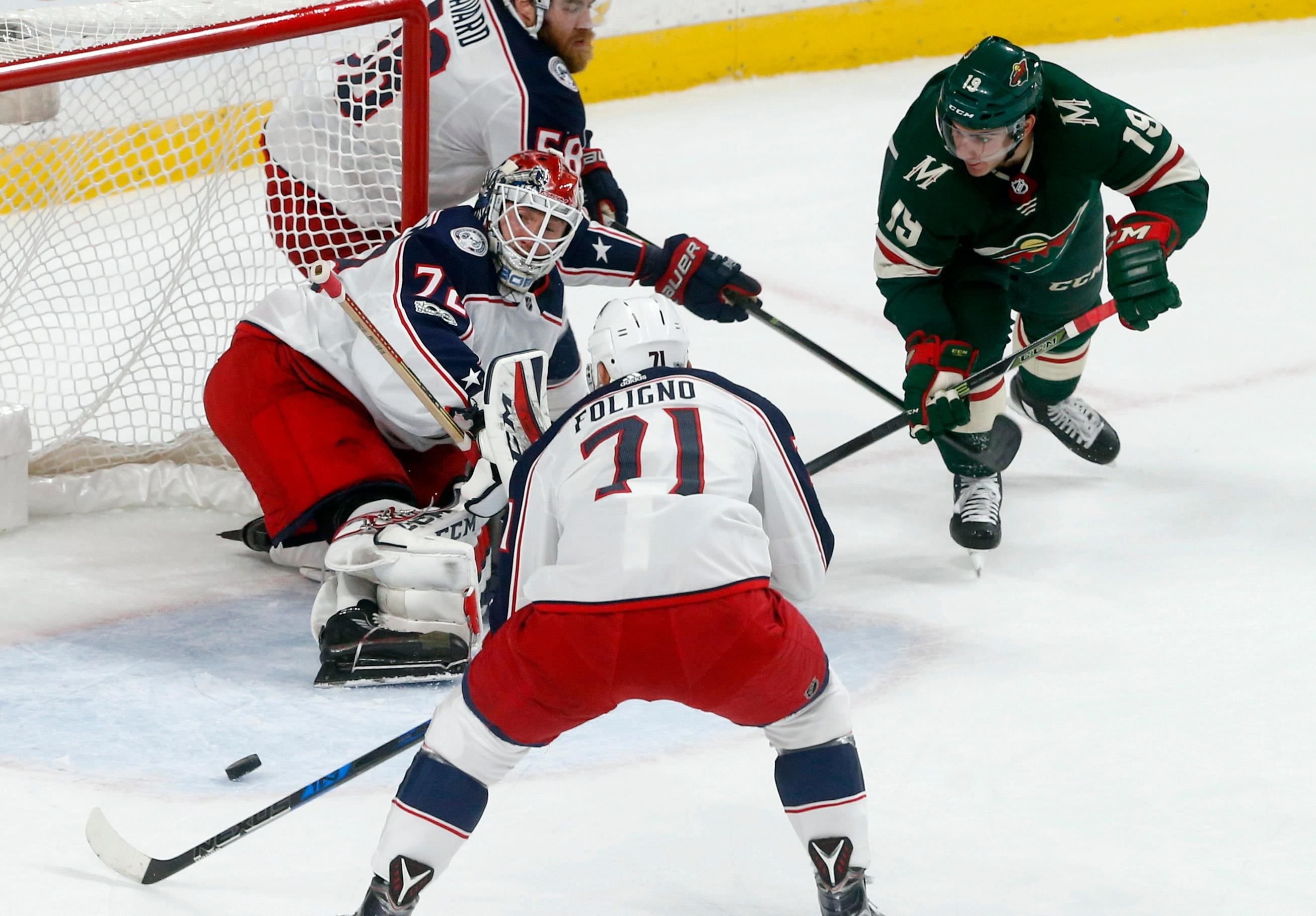 Columbus Blue Jackets goalie Sergei Bobrovsky, left, of Russia, stops a shot as Minnesota Wild's Luke Kunin, right, looked for a rebound during the first period of an NHL hockey game Saturday, Oct. 14, 2017, in St. Paul, Minn. (AP Photo/Jim Mone)