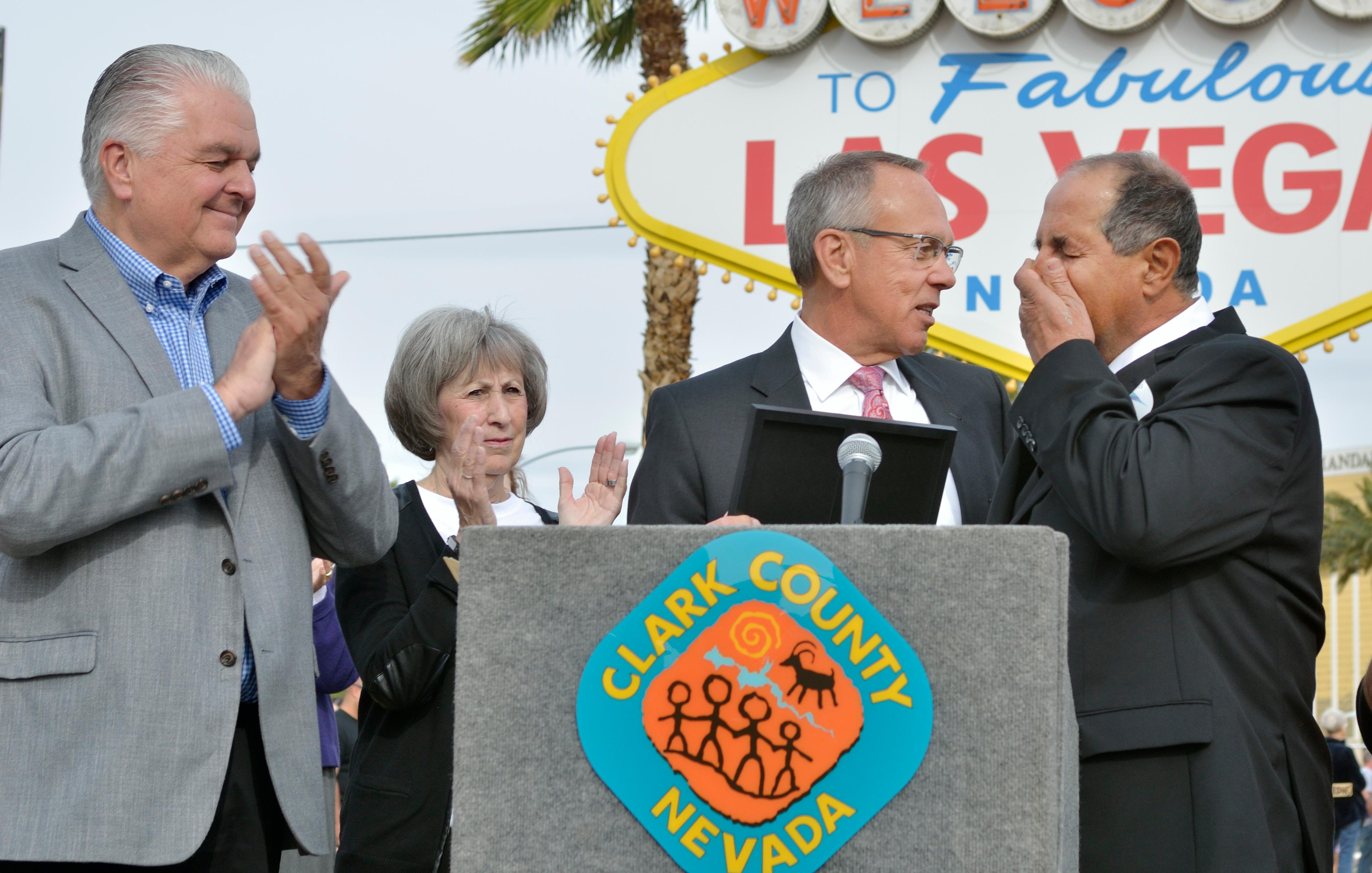 "Greg Zanis, right, is overcome with emotion while being honored by Clark County commissioners, including, from left, Steve Sisolak, Susan Brager and Jim Gibson during ""Greg Zanis Day"" at the Welcome to Fabulous Las Vegas sign on the Las Vegas Strip on Sunday, Nov. 12, 2017. Zanis, a carpenter from Aurora, Ill., was recognized by the Clark County Commision for creating 58 crosses memorializing those who died during the Route 91 Harvest festival shooting on Oct. 1. The crosses were later moved to the Clark County Museum for its permanent collection. [Bill Hughes/Las Vegas News Bureau]"