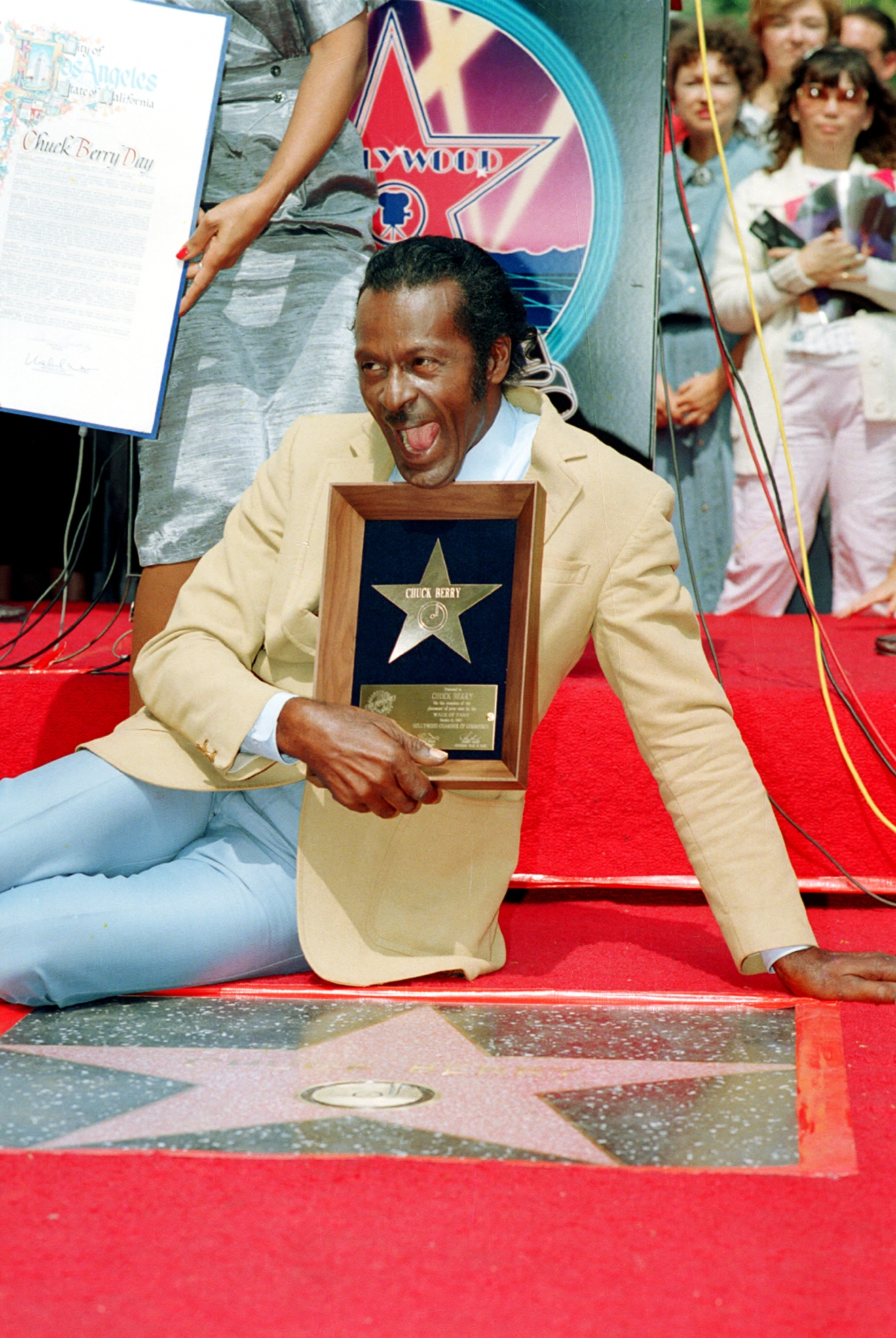 Rock and roll musician Chuck Berry laughs as he poses with his plaque after receiving the Hollywood Walk of Fame star in Hollywood, Ca., Oct. 8, 1987.  Berry received the 1,857th star on the boulevard.  (AP Photo/Mark Terrill)