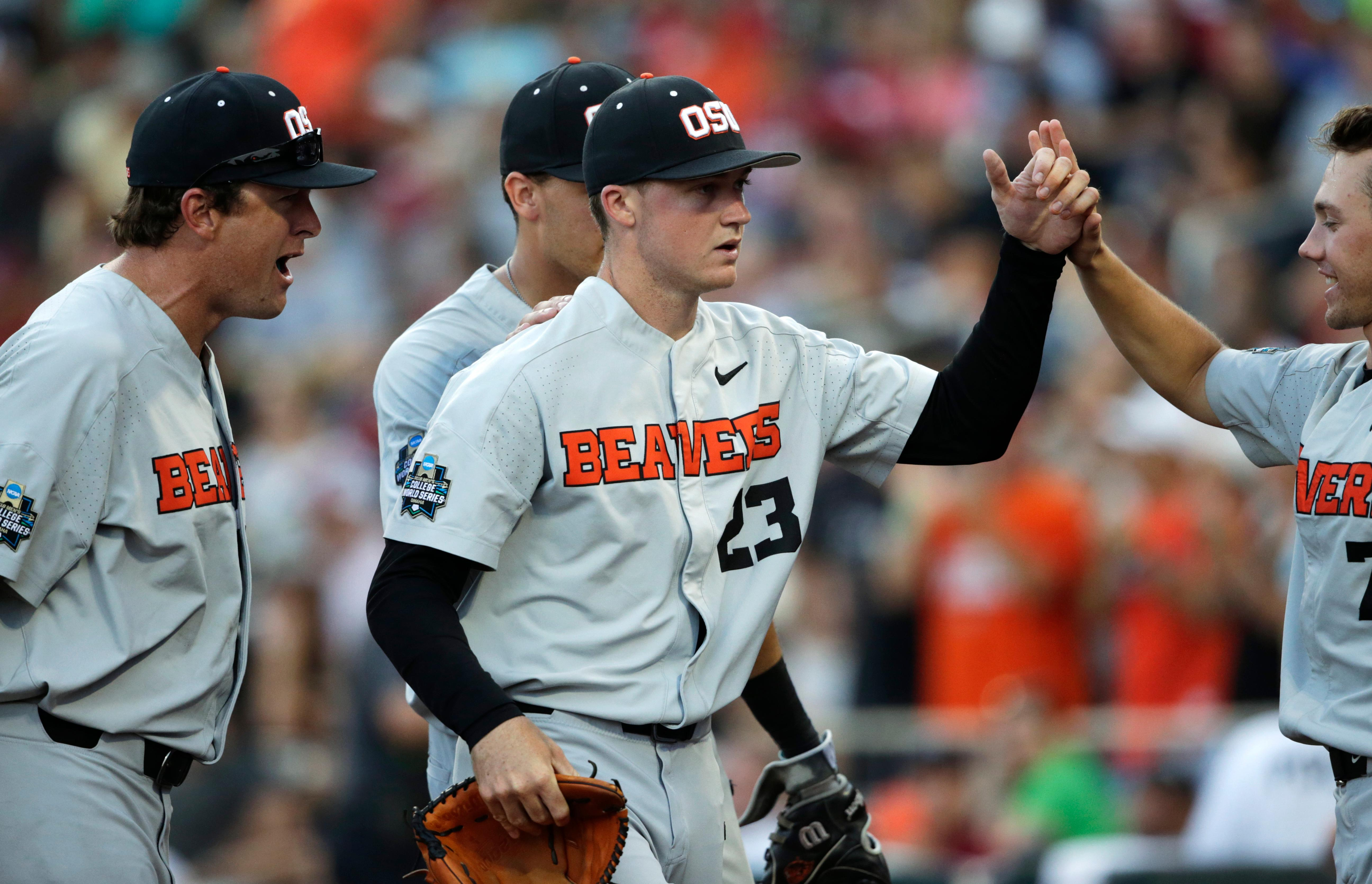 Oregon State pitcher Kevin Abel, center, is greeted by teammates at the end of the eighth inning of Game 3 against Arkansas in the NCAA College World Series baseball finals, Thursday, June 28, 2018, in Omaha, Neb. (AP Photo/Nati Harnik)