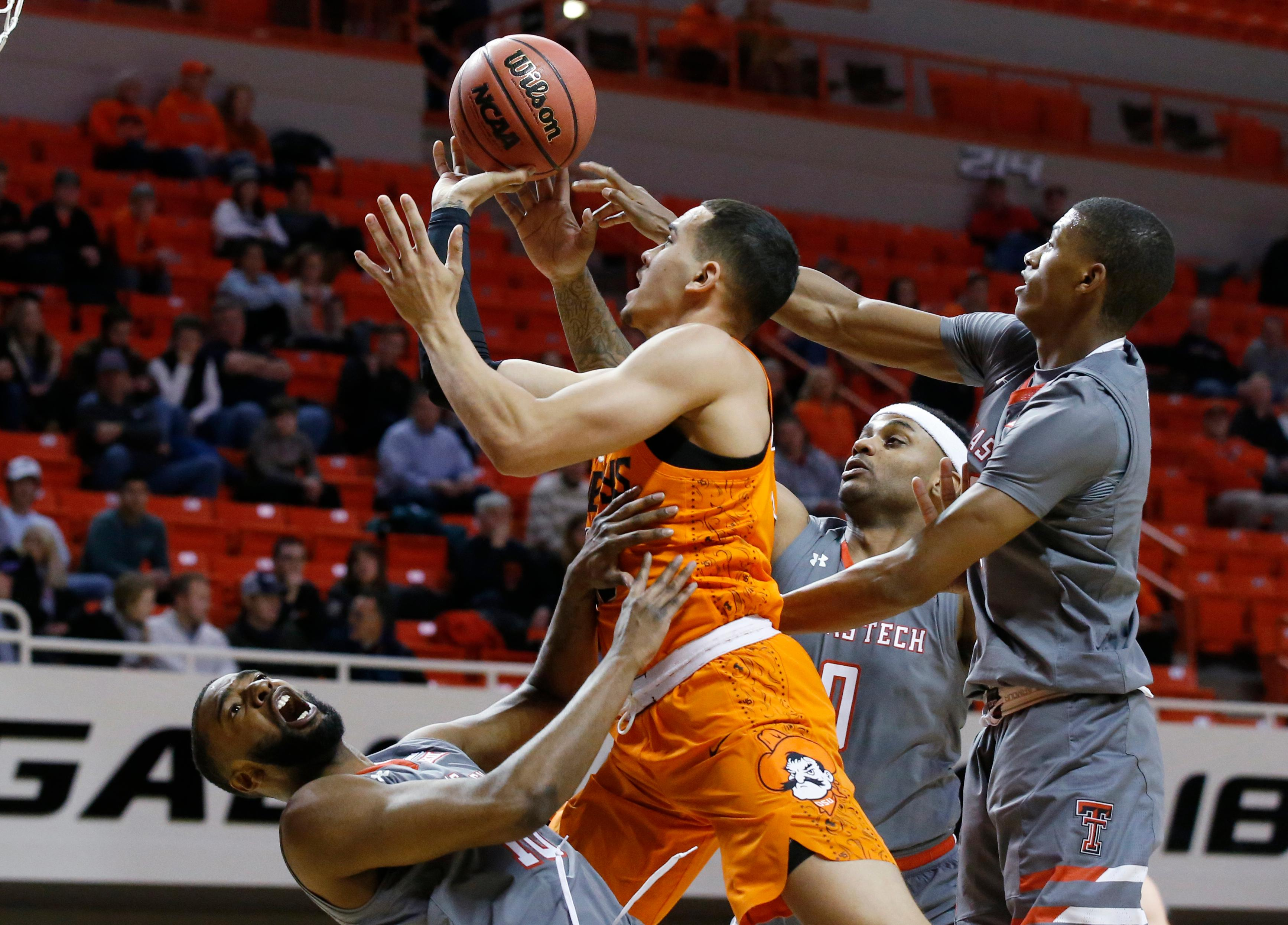 Oklahoma State guard Jeffrey Carroll, center, fouls Texas Tech guard Niem Stevenson, left, as he drives to the basket between Stevenson, guard Jarrett Culver, right, and forward Tommy Hamilton IV (0) during the first half of an NCAA college basketball game in Stillwater, Okla., Wednesday, Feb. 21, 2018. (AP Photo/Sue Ogrocki)