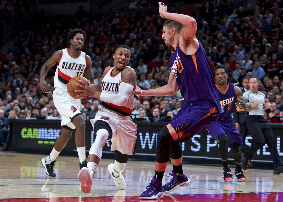 Portland Trail Blazers guard Damian Lillard, center, drives to the basket past Phoenix Suns center Alex Len during the first half of an NBA basketball game in Portland, Ore., Tuesday, Nov. 8, 2016. (AP Photo/Craig Mitchelldyer)