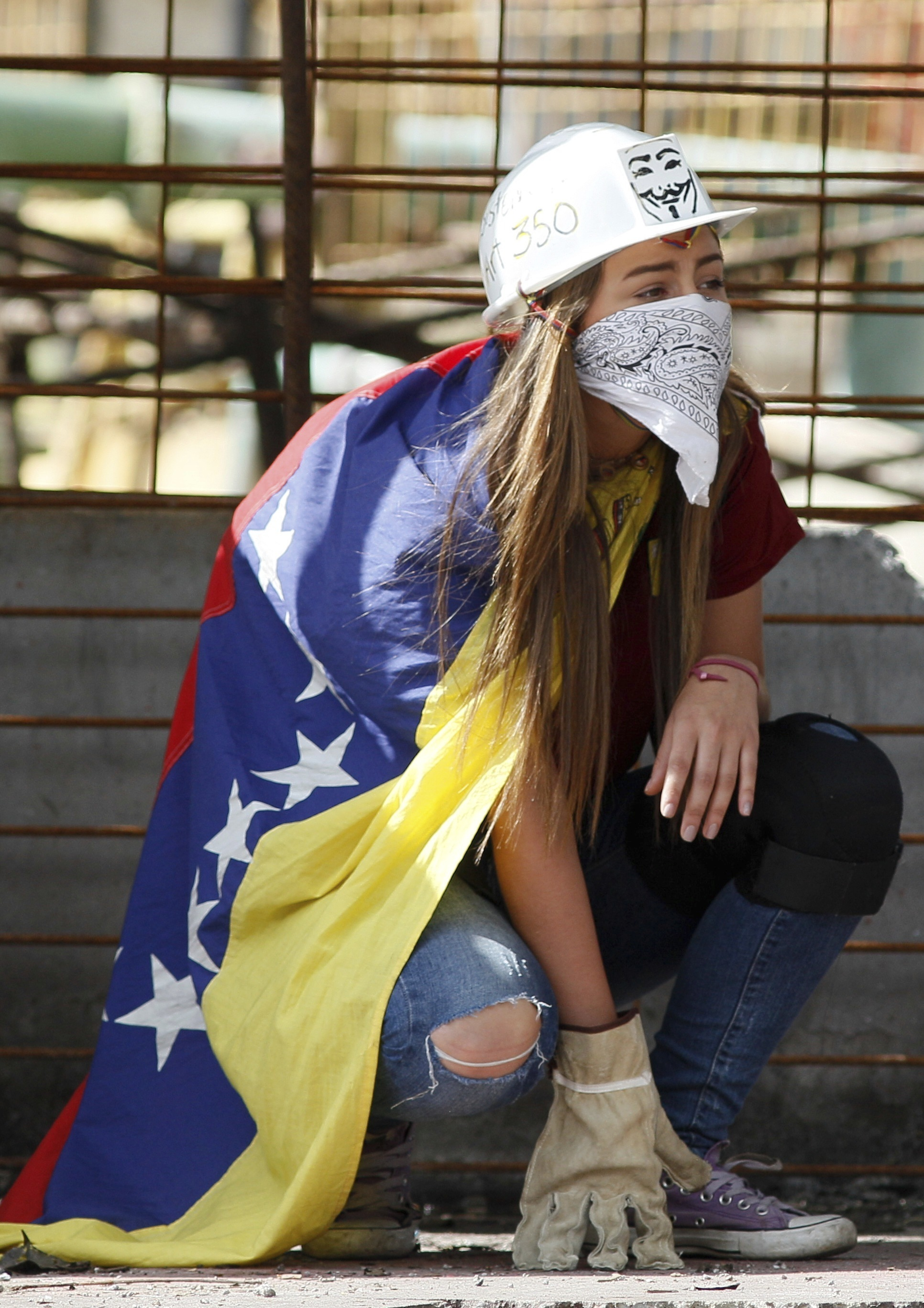An anti-government demonstrator wears a Venezuelan flag, helmet, bandana and gloves during clashes against Bolivarian National Guards in Caracas, Venezuela, Friday, July 28, 2017, two days before the vote to begin the rewriting of Venezuela's constitution. Protesters say the election of a constitutional assembly will allow President Nicolas Maduro to eliminate democratic checks and balances and install an authoritarian single-party system. (AP Photo/Ariana Cubillos)