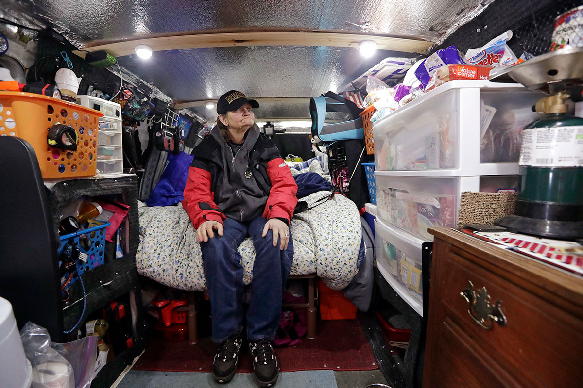 In this Monday, March 5, 2018, photo, Tamara Bancroft sits inside her van, where she lives with her partner among the two-dozen or so vehicles housing homeless single women in a church parking lot in Kirkland, Wash. Some of the obstacles faced by the women in finding permanent housing may soon become illegal in Washington state, where legislators are advancing a bill that would prohibit landlords from turning away tenants who rely on Section 8 vouchers, Social Security or veterans benefits. (AP Photo/Elaine Thompson)