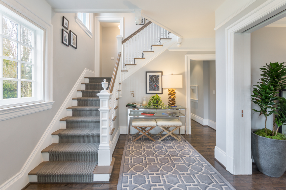The entrance of the Ambrose welcomes you with original walnut floors and a split staircase showcasing the home's original millwork details.   The home has been updated with new systems all-new plumbing, electrical and mechanical systems, including hydronic in-floor heat on the main floor.