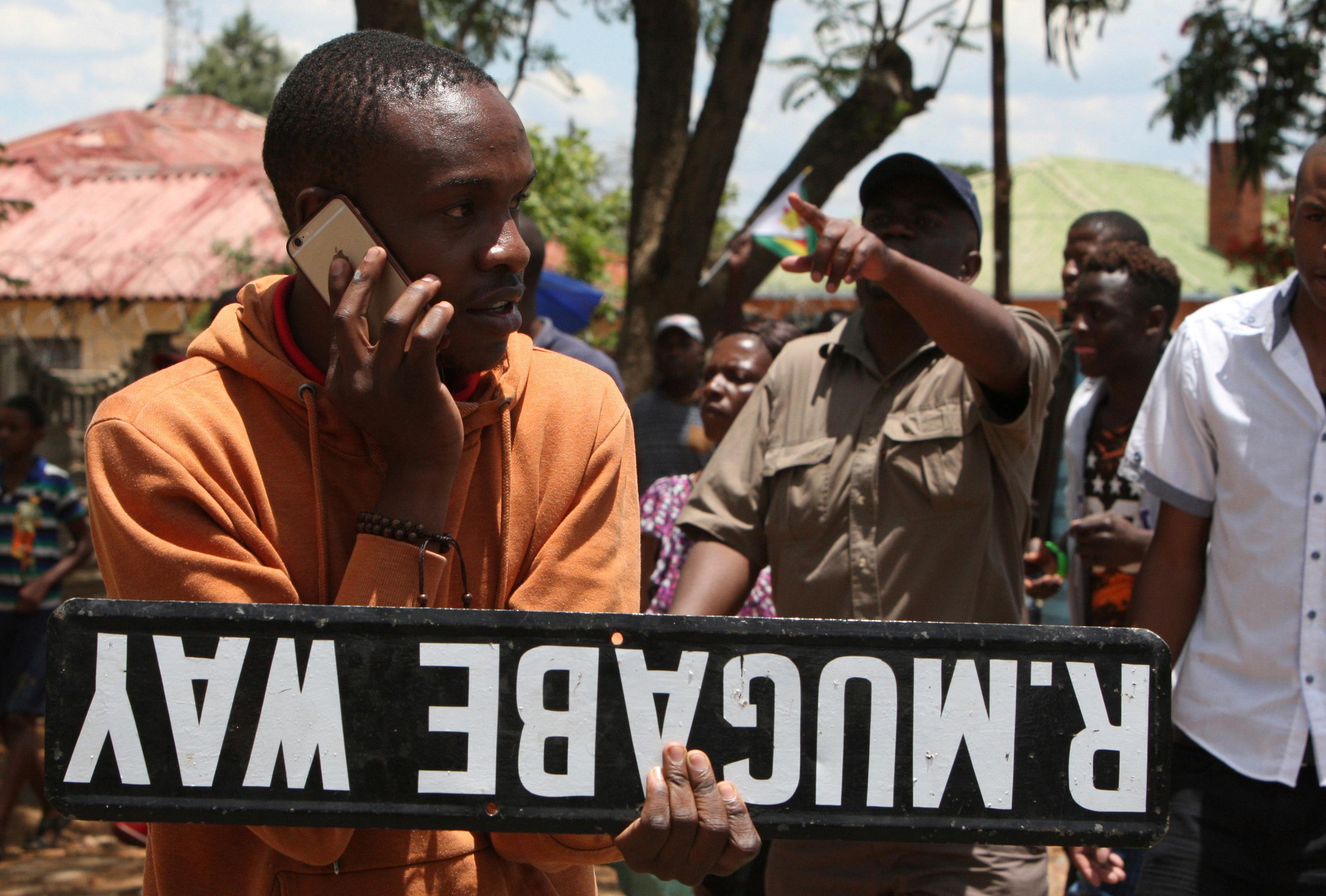 A man holds a street sign as hundreds gather in Bulawayo, Zimbabwe, Saturday, Nov. 18, 2017 to demand the departure of President Robert Mugabe after nearly four decades in power. (AP Photo/Lucky Tshuma)