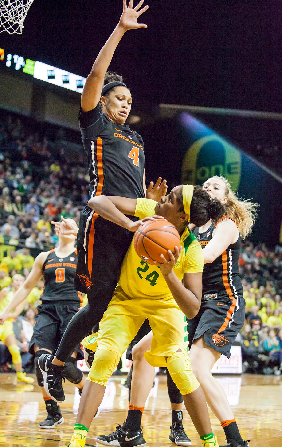 Oregon forward Ruthy Hebard (#24) looks to make a pass around Oregon Stare center Breanna Brown (#4). The Oregon Ducks lost 40 to 43 against the Oregon State Beavers after a tightly matched 4th quarter. Photo by Ben Lonergan, Oregon News Lab