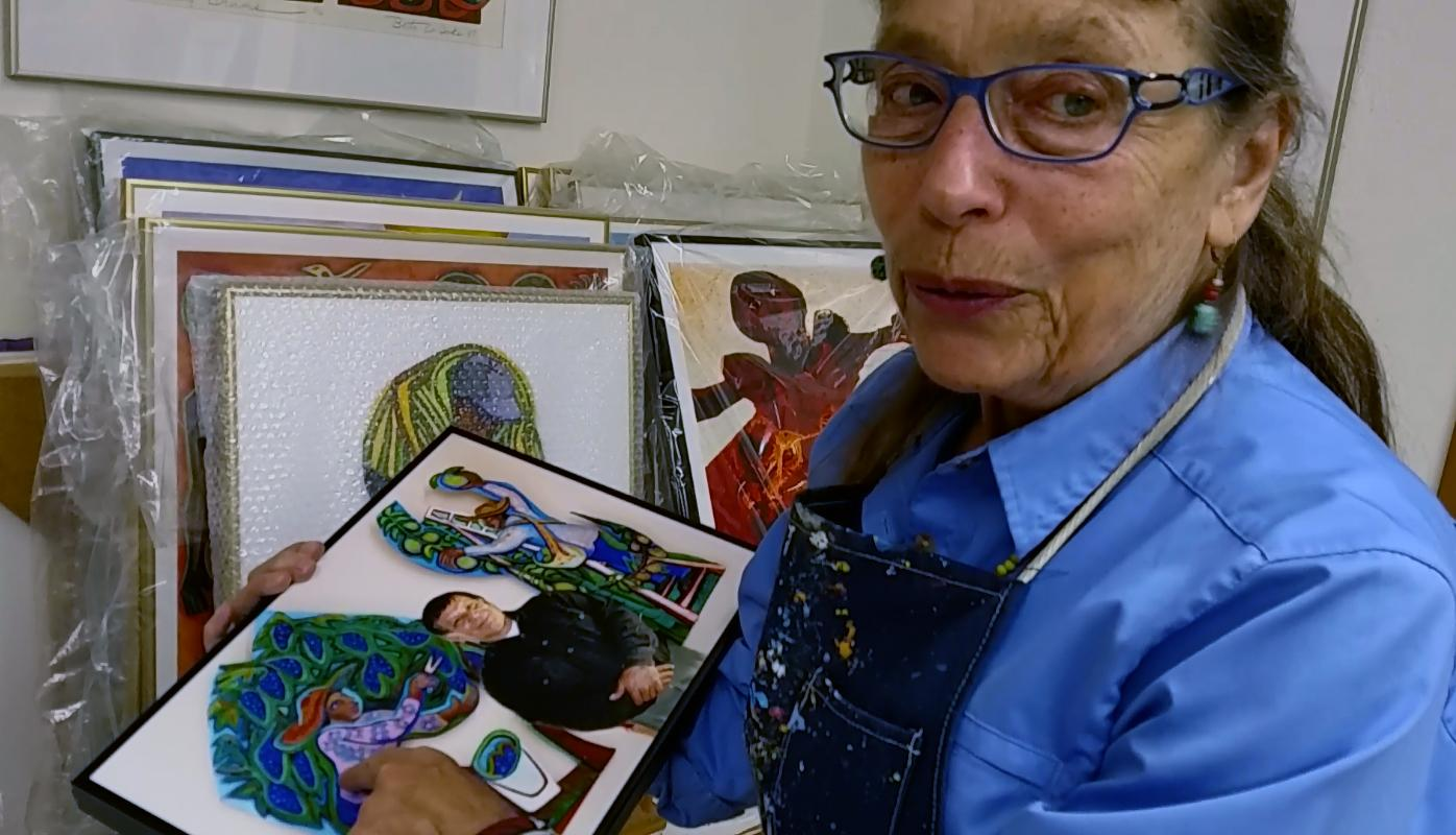 Betty LaDuke holds a photograph of Oscar, a vineyard worker at Quail Run Vineyards, standing by the wooden art panel Betty created of his image. (Photo by Maureen Flanagan Battistella)