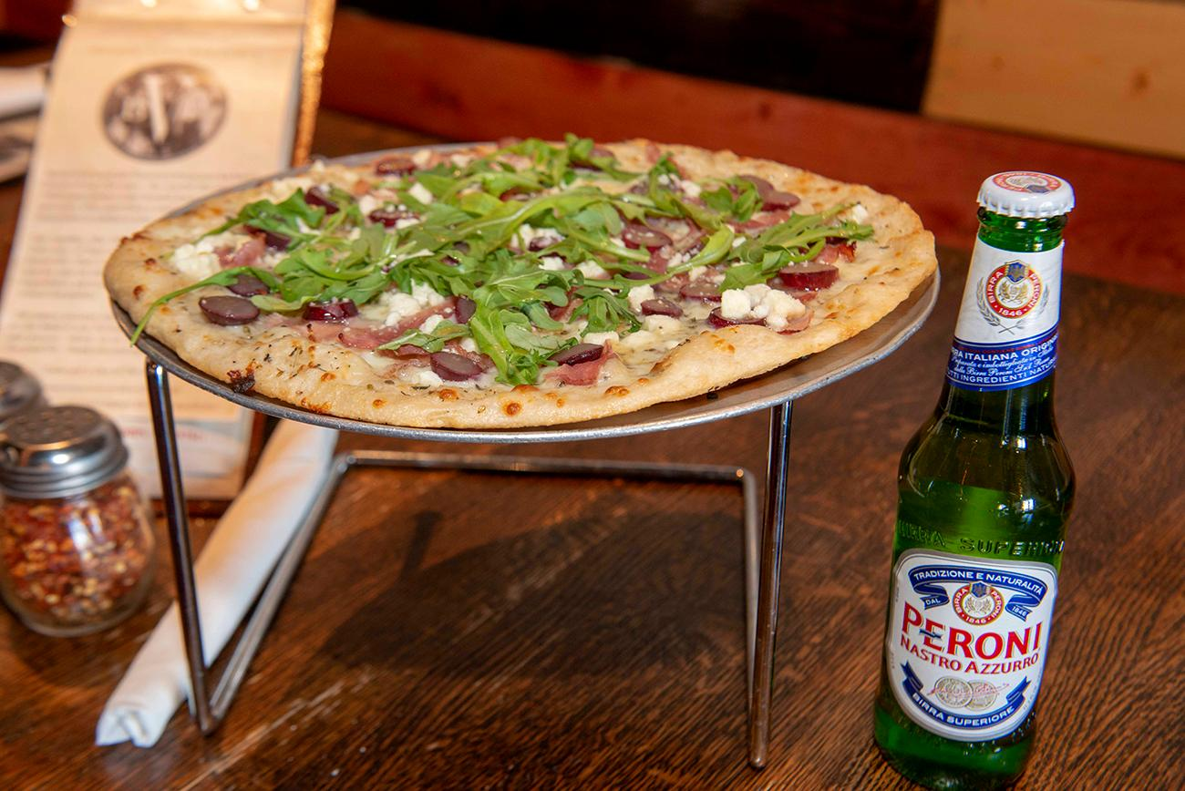 Grape truffle pizza served with a bottle of Peroni{ }/ Image: Joe Simon // Published: 3.10.19
